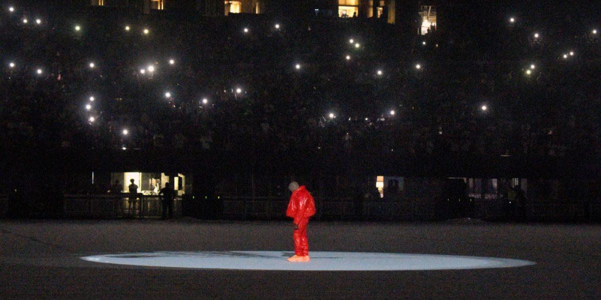 Kanye West, seul en doudoune et pantalon rouges au milieu du Mercedes-Benz Stadium à Atlanta pour la première listening party de Donda.